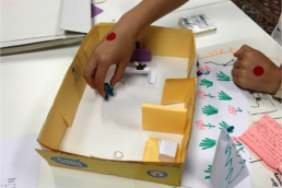 Student playing with a paper prototype